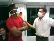 Dos jovenes se cuidan de no contraer la temida gripe AH1N1 por multitud en el metro de Santo Domingo